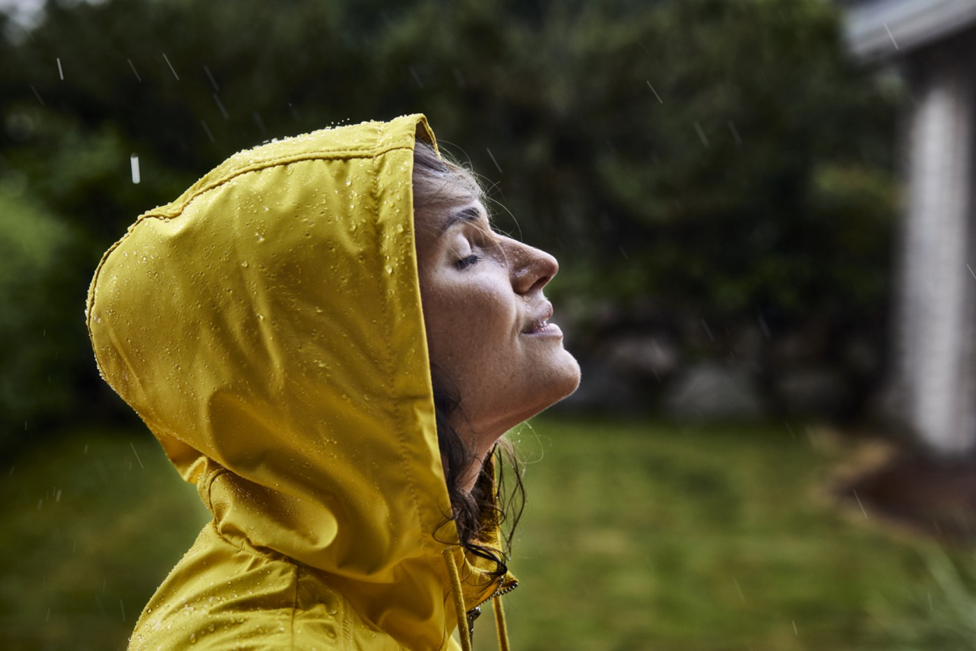 A photo of a woman wearing a raincoat and hood. She is standing in the rain with her eyes closed, looking peaceful.