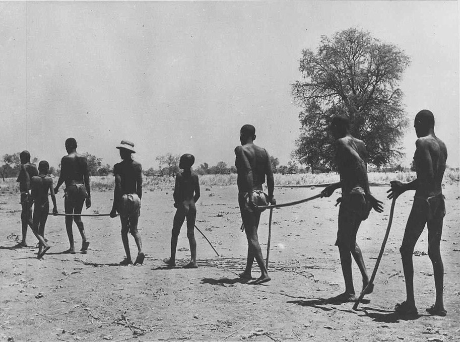 In Africa, blind adults are led through a desert-like environment by children.
