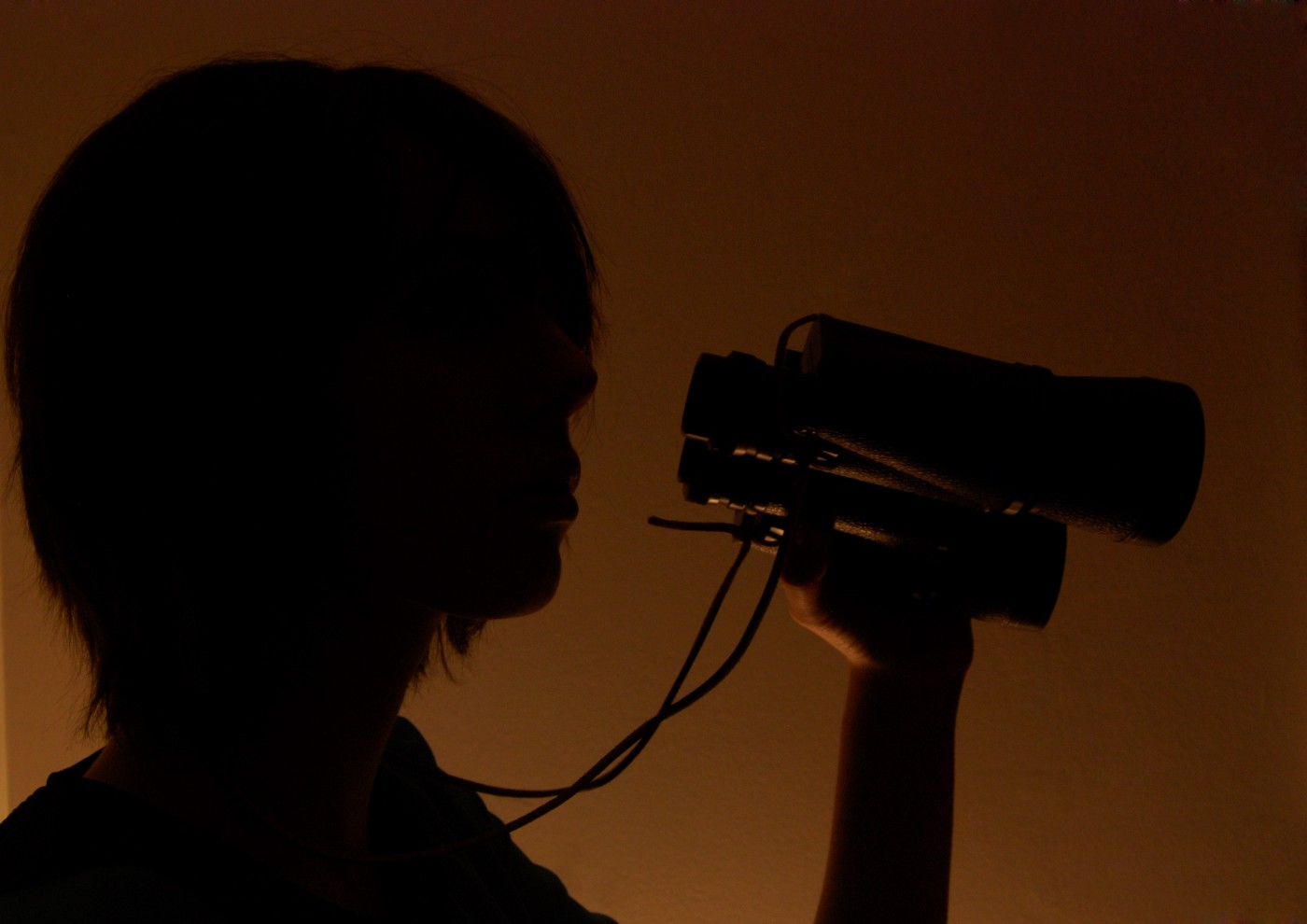 A person with shoulder length hair lit from behind, appearing like a shadow, holding a pair of binoculars