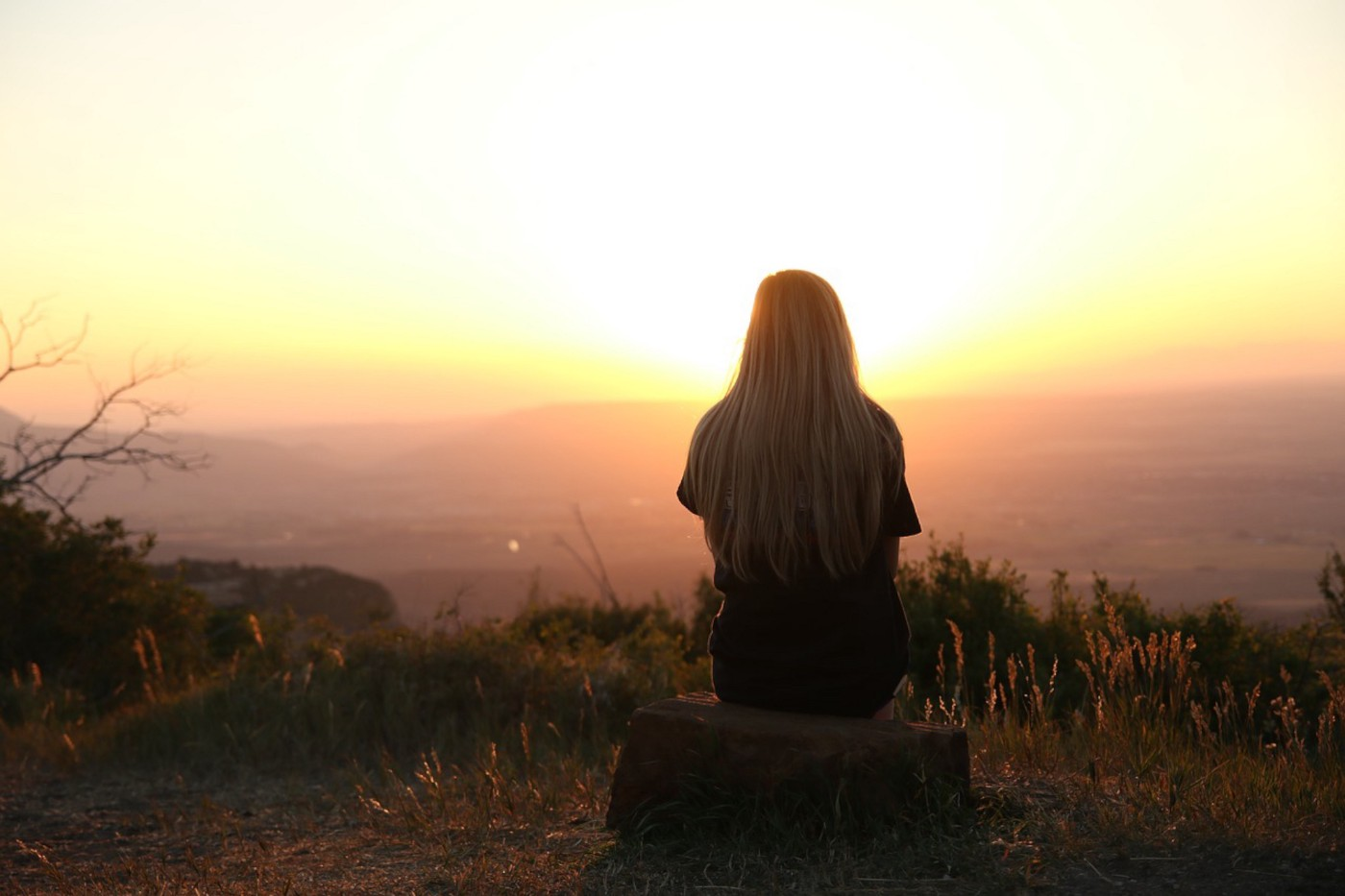 Photo of a woman, watching the sun set, while sitting in a field on a tree trunk.