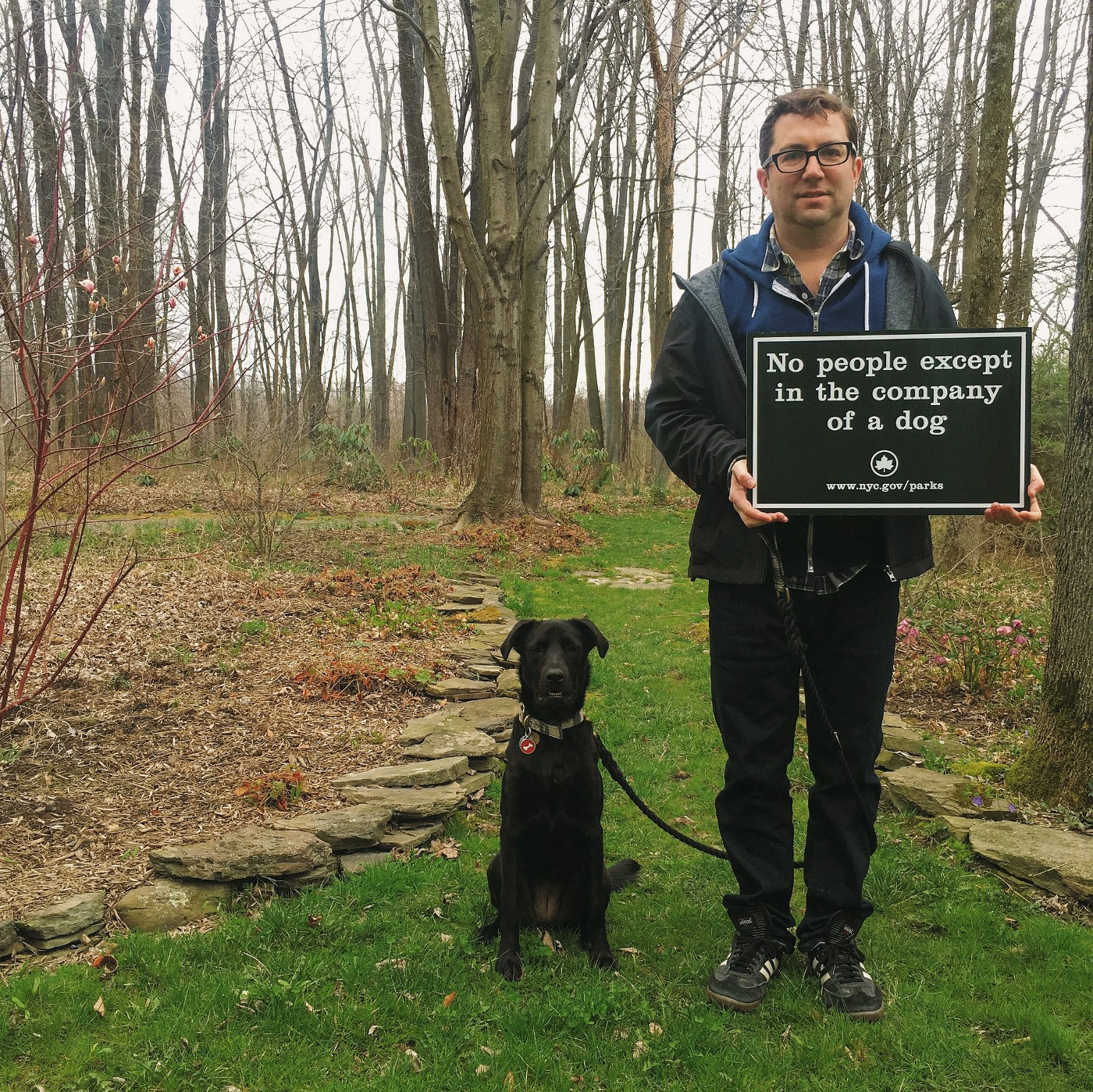 Mat and Nora in the garden holding a sign about no people entering without pets