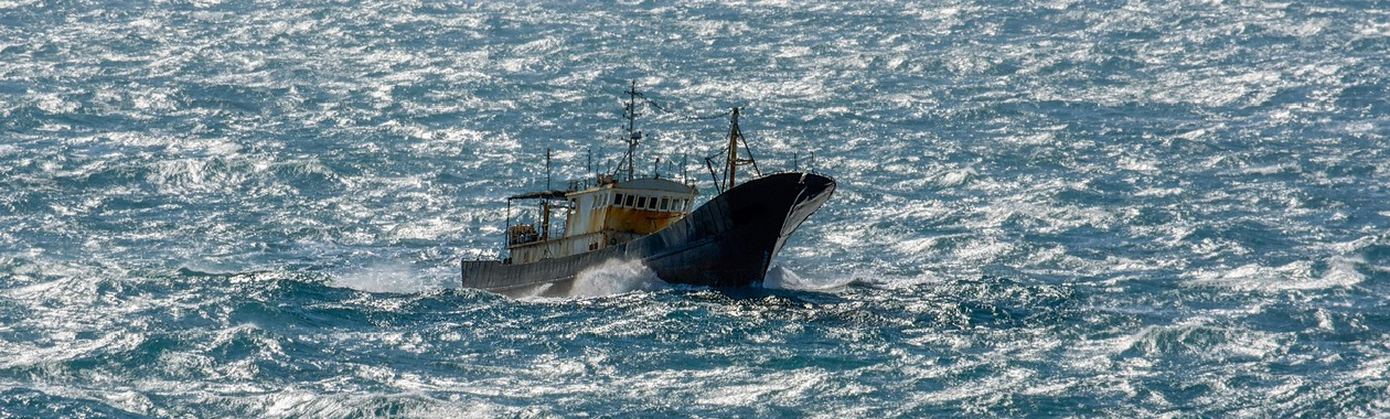 Small chinese trawler pounds through rough seas as it crosses the South China sea.