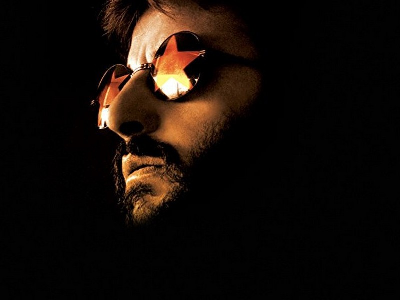 Picture of Ringo Starr wearing glasses in dark lighting