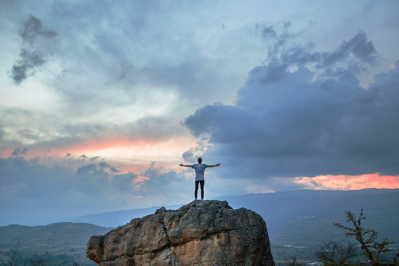 A man stands on a large rock with his hands spread eagle in front of the wide open skies and mountains