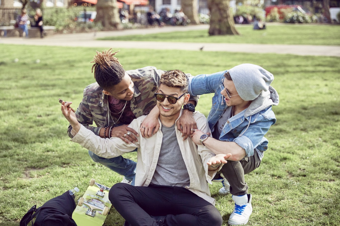A teenage boy shrugs as his friends laugh in a circle around him at the park.