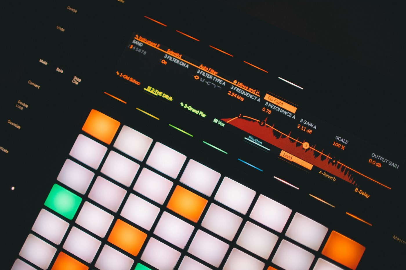 image of an electronic step sequencer, screen and pads lit up in the dark