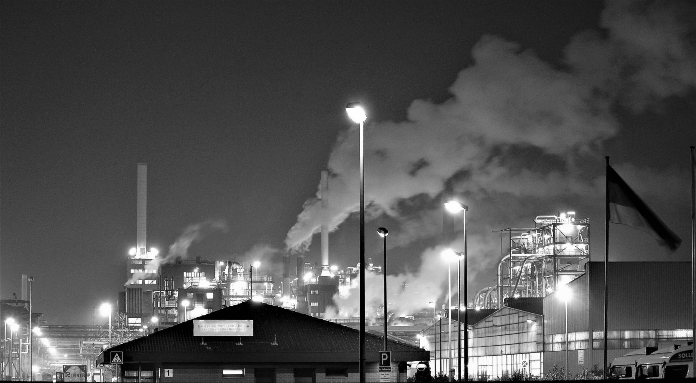 grayscale image of a factory releasing fumes into the atmosphere