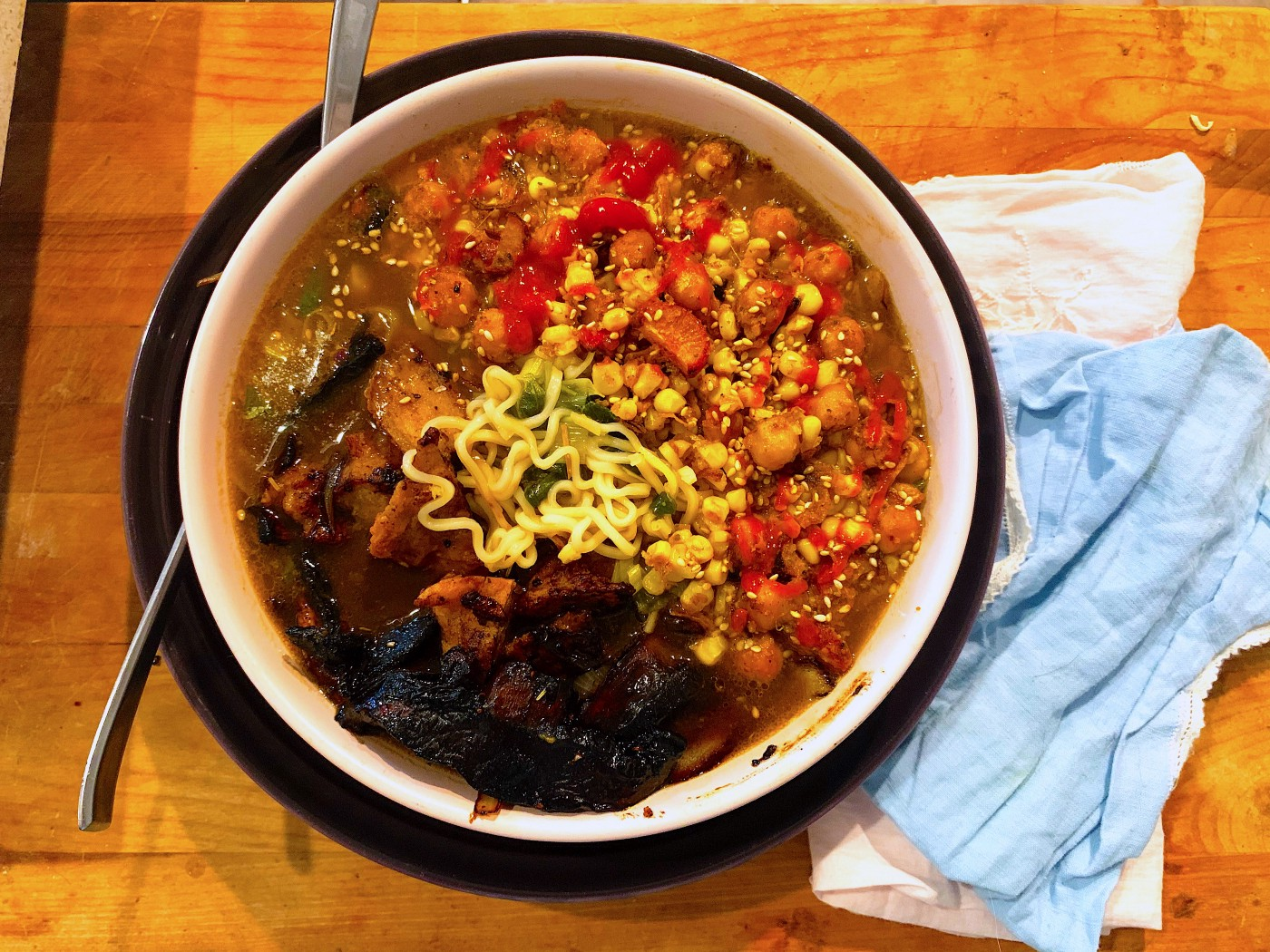 vegetable ramen noodle bowl with chickpeas, blackened mushrooms, and noodles peeking out from the broth