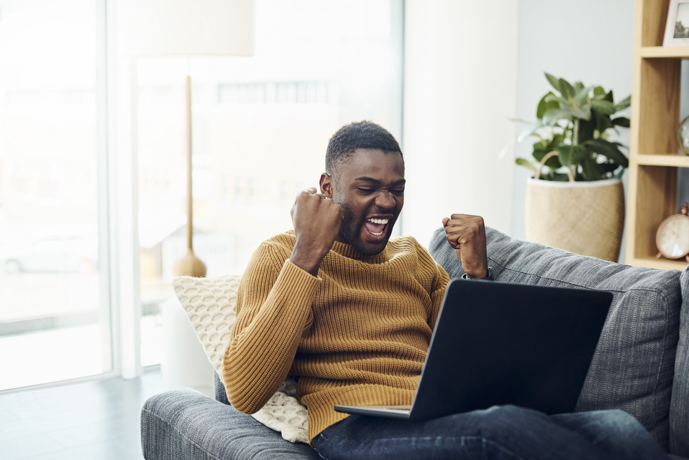 A young man cheers while using a laptop at home on his couch.