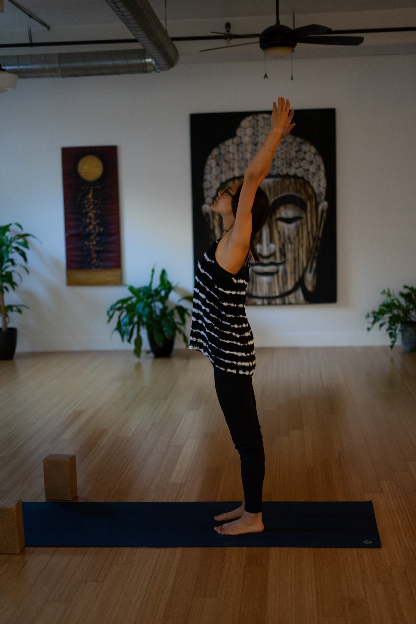 A woman standing in the middle of a brightly lit yoga studio. She is reaching up with her arms and gazing upward. In the background are two large paintings and three plants in pots.
