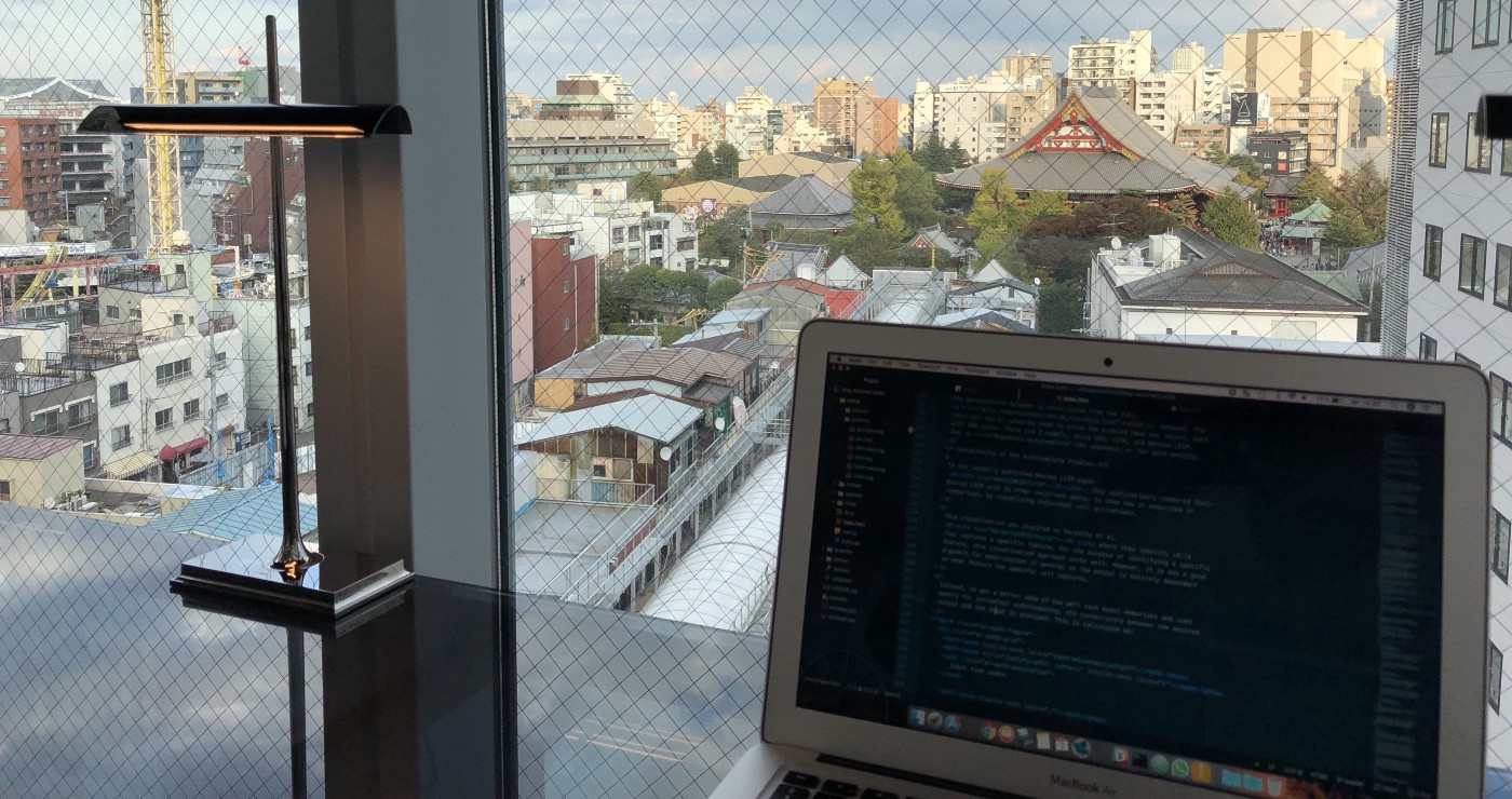 Picture of my computer with the HTML code for my distill.pub publication. Background is a window showing Tokyo, Japan.