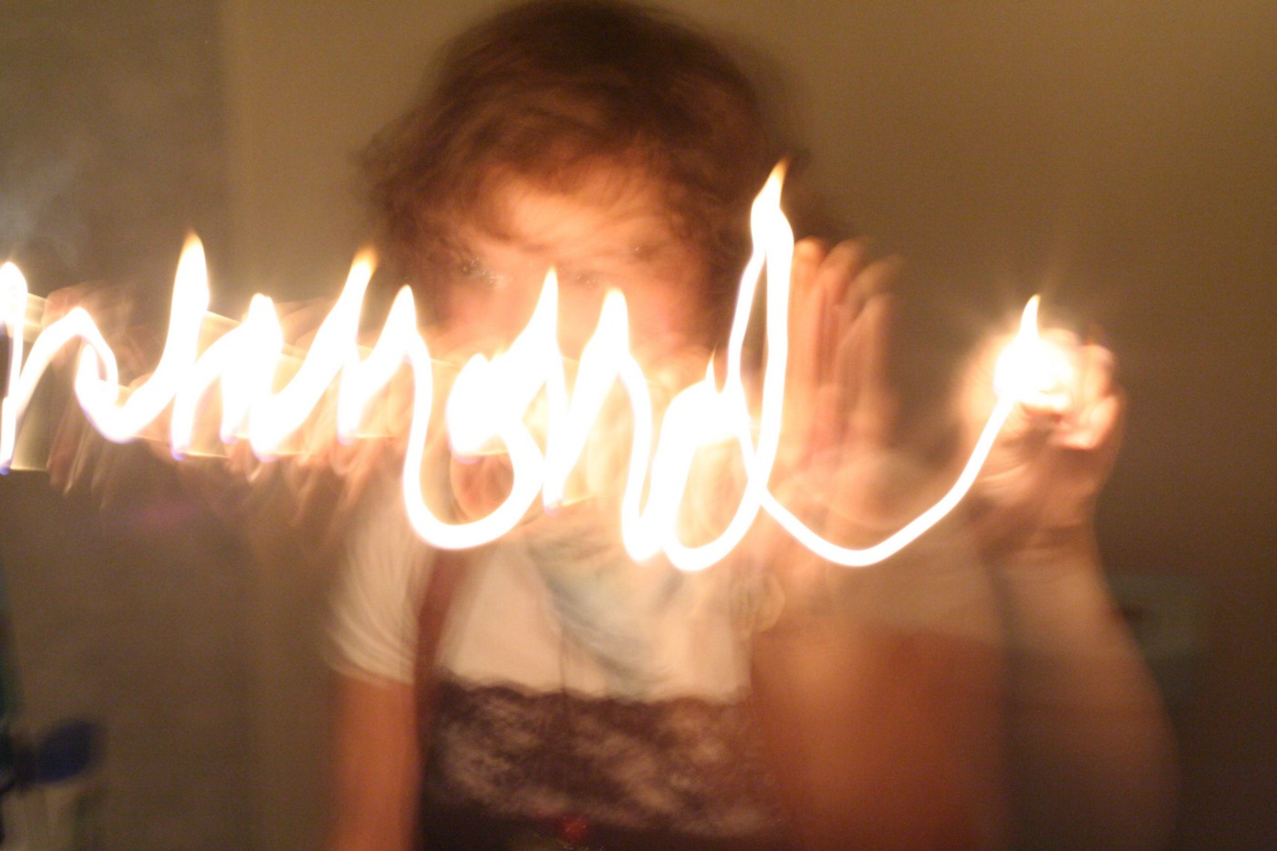 A blurry long-exposure photo of a person writing with light.