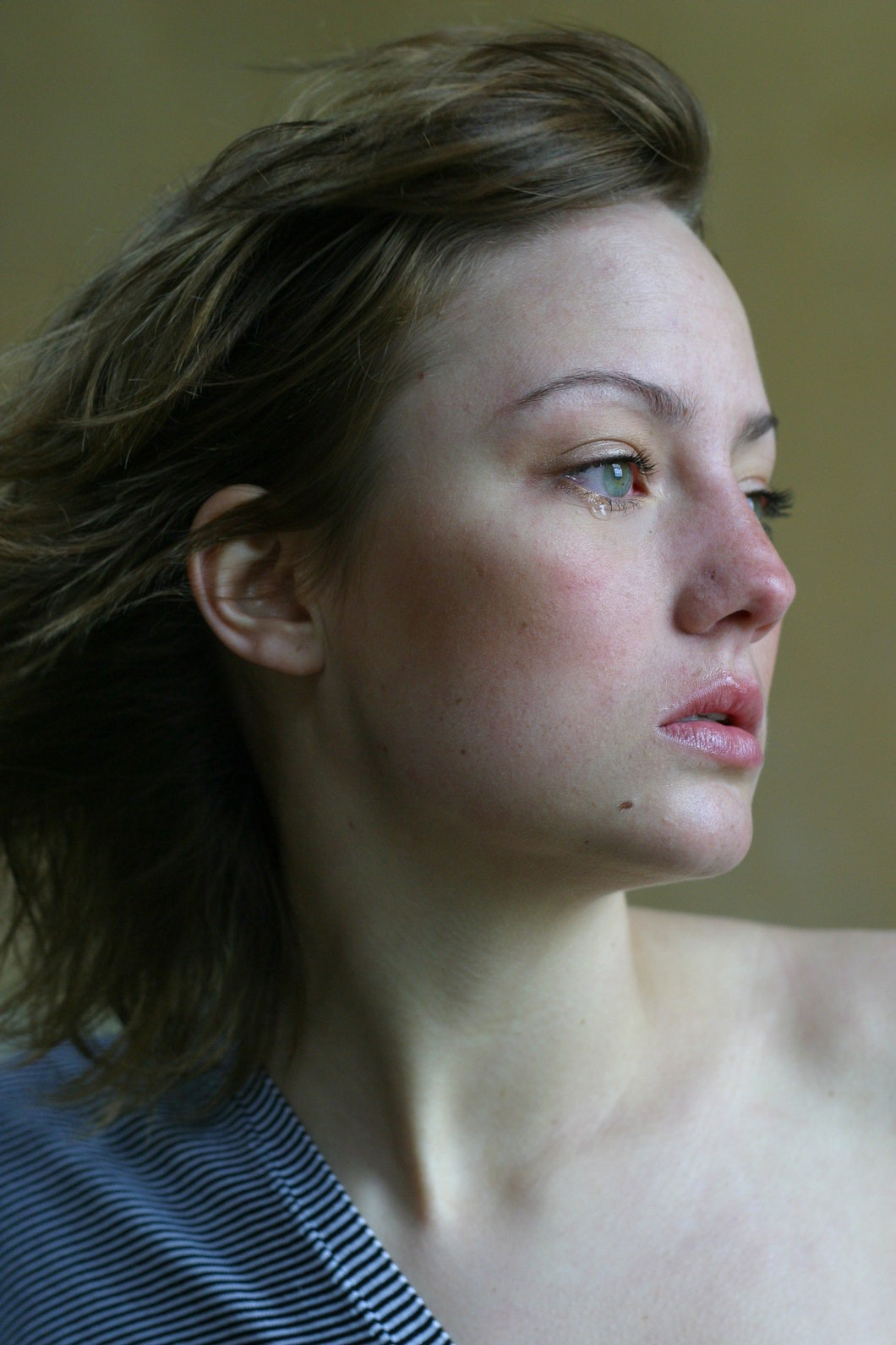 Woman with her head turned to the left with a tear dropping from her eye