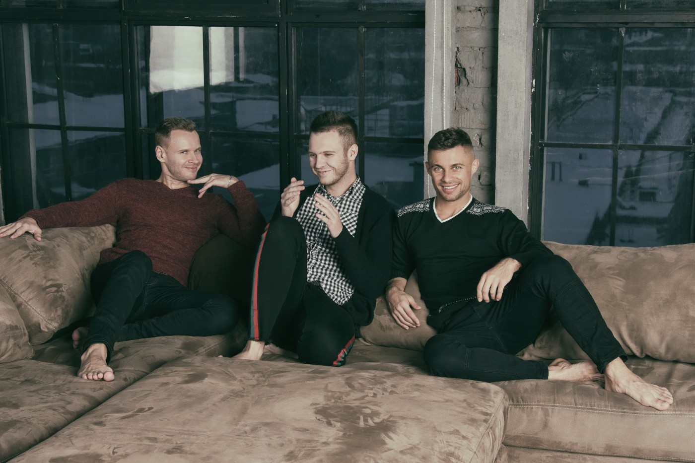 A photo of three handsome, gay men sitting barefoot next to each other on a huge sofa.