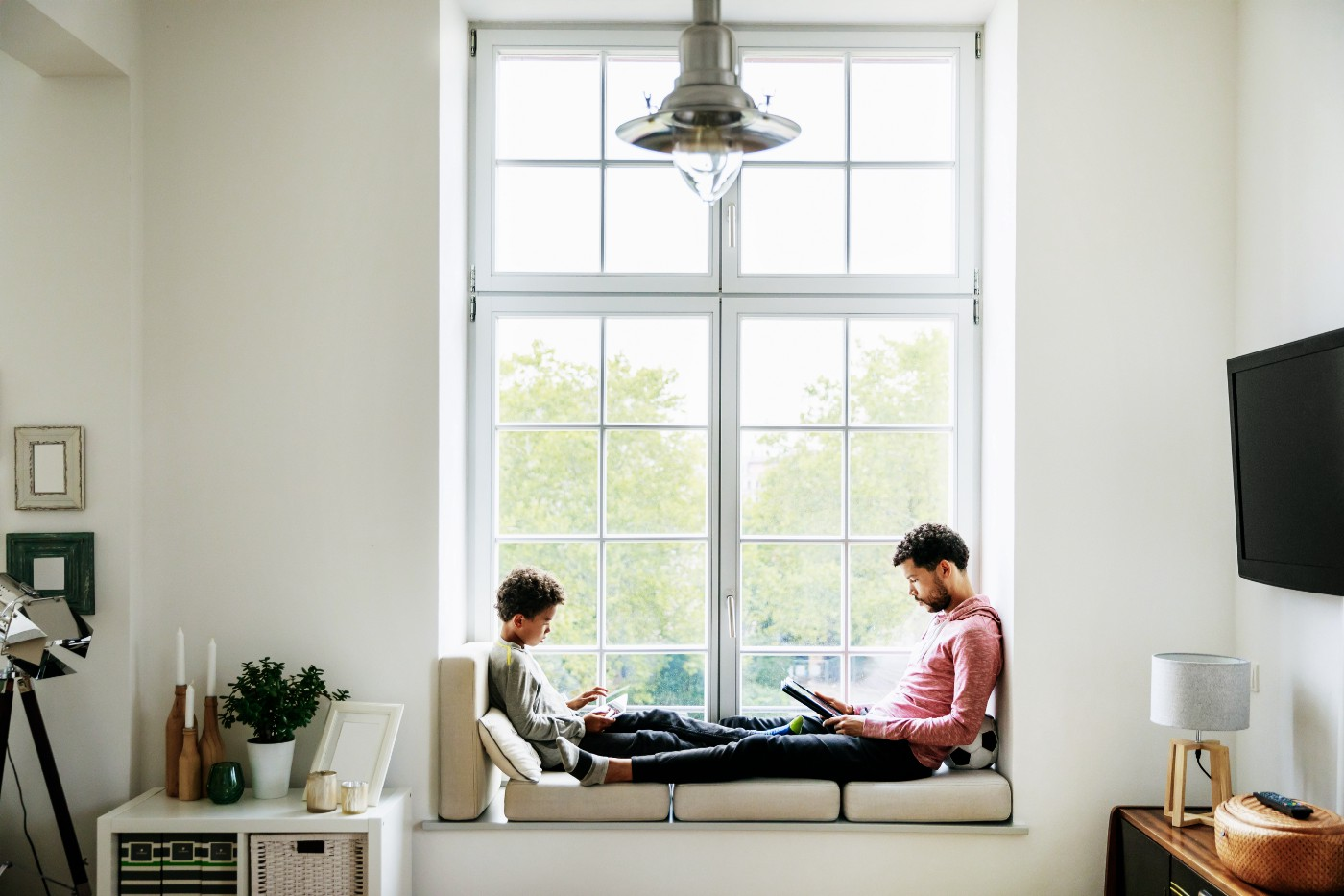 A father and son are relaxing by a large window at home, reading and playing games together.