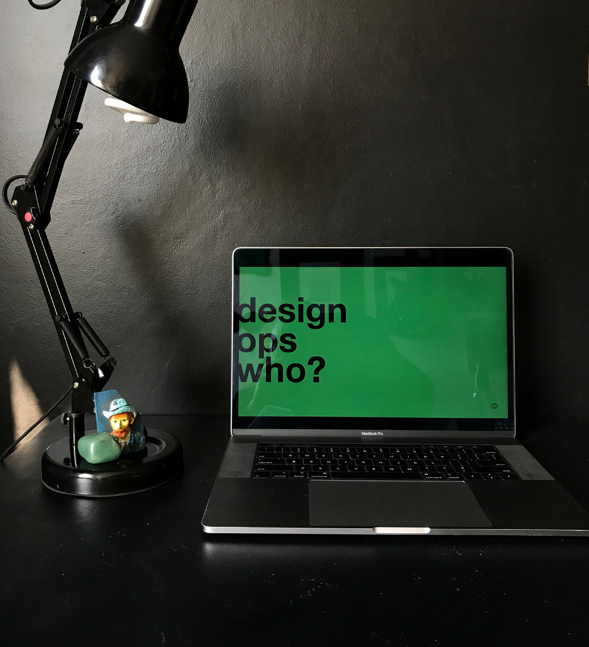 a laptop on a table. on the screen there's a Creditas green slide with the text: design ops who?