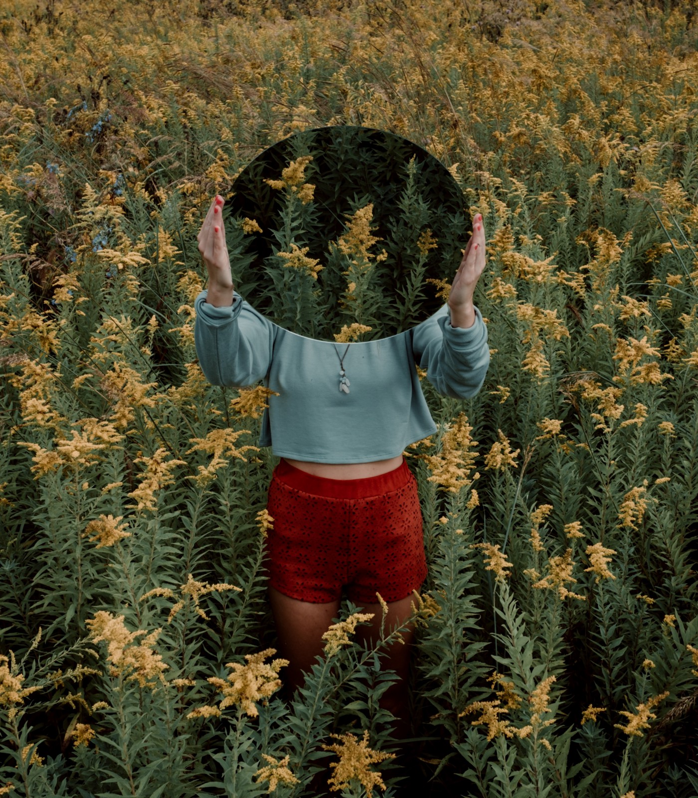 Girl holding oval mirror over her face, reflecting the field of yellow flowers she's standing in