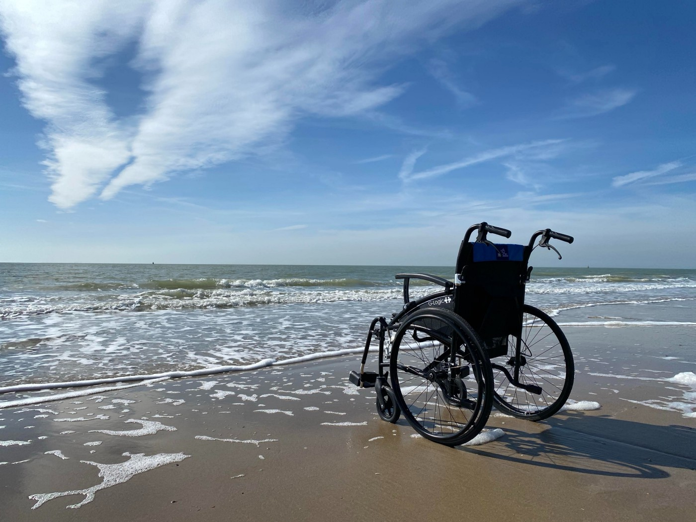 A wheelchair by the ocean; waves are lapping up the beach under a blue sky