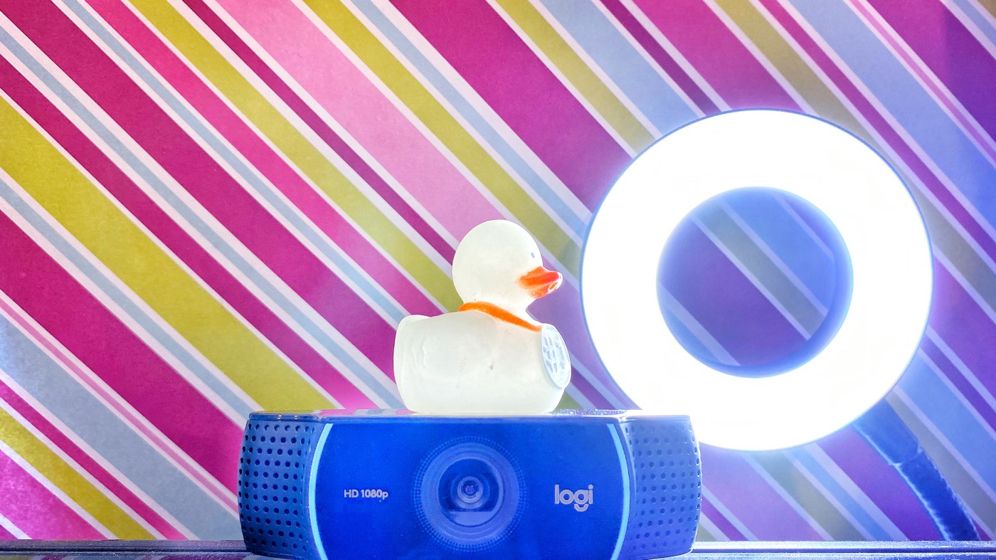 a rubber duckie on top of a webcam, with a ring light behind it, against a colorful backdrop