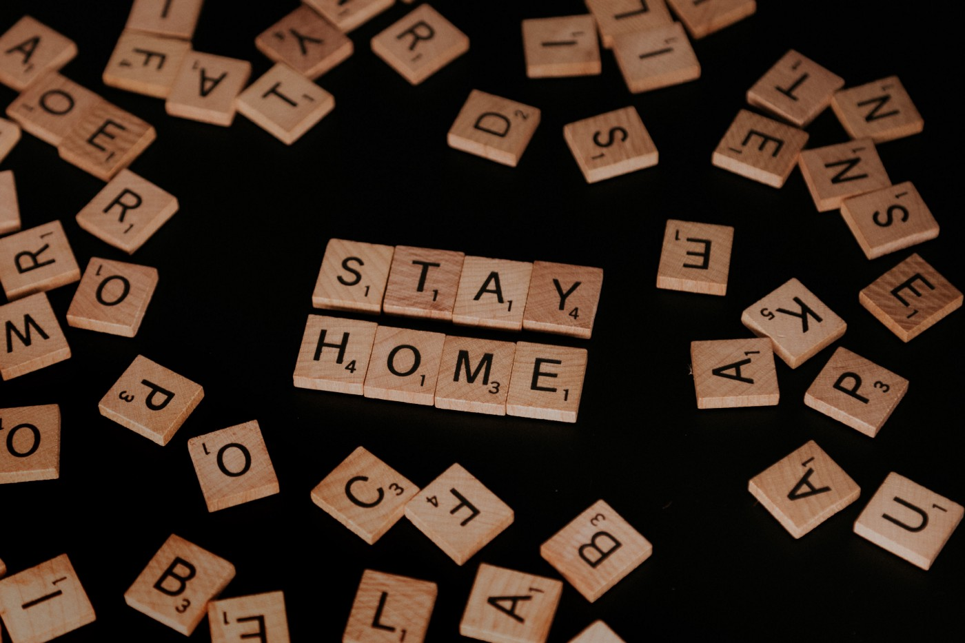 """A scrabble board with the words """"STAY HOME"""" spelled out."""