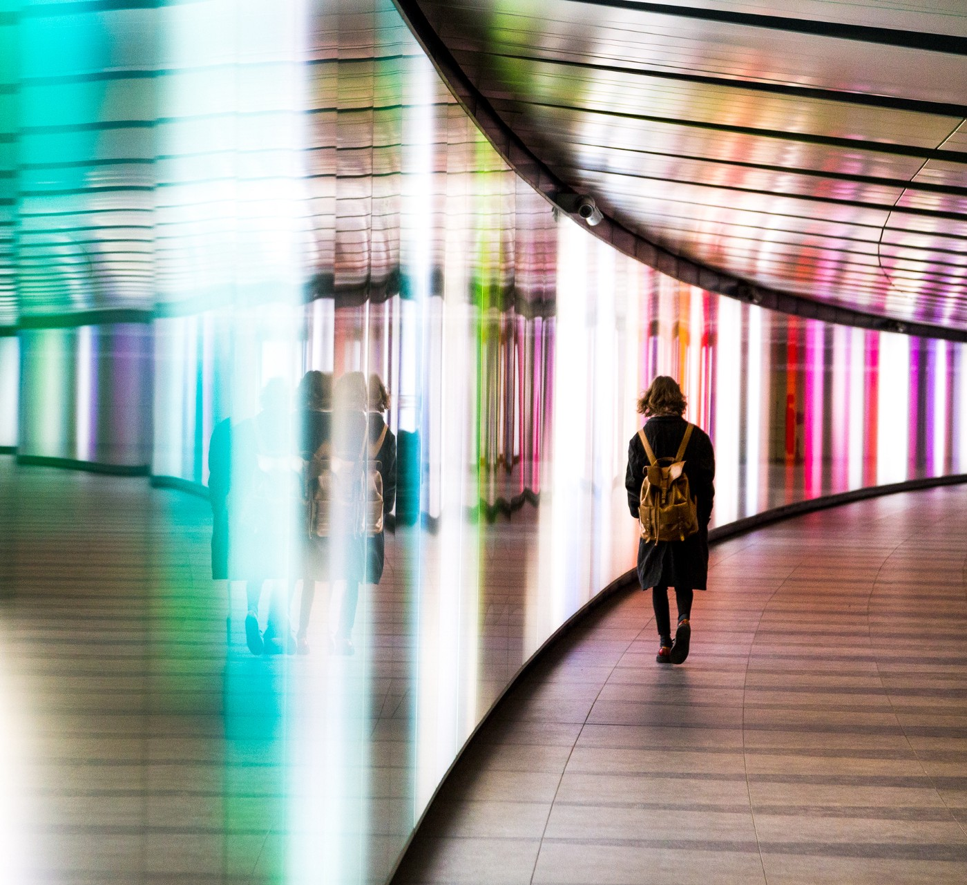 A photo of a woman with a backpack on walking through a bright rainbow-lit curved hallway.