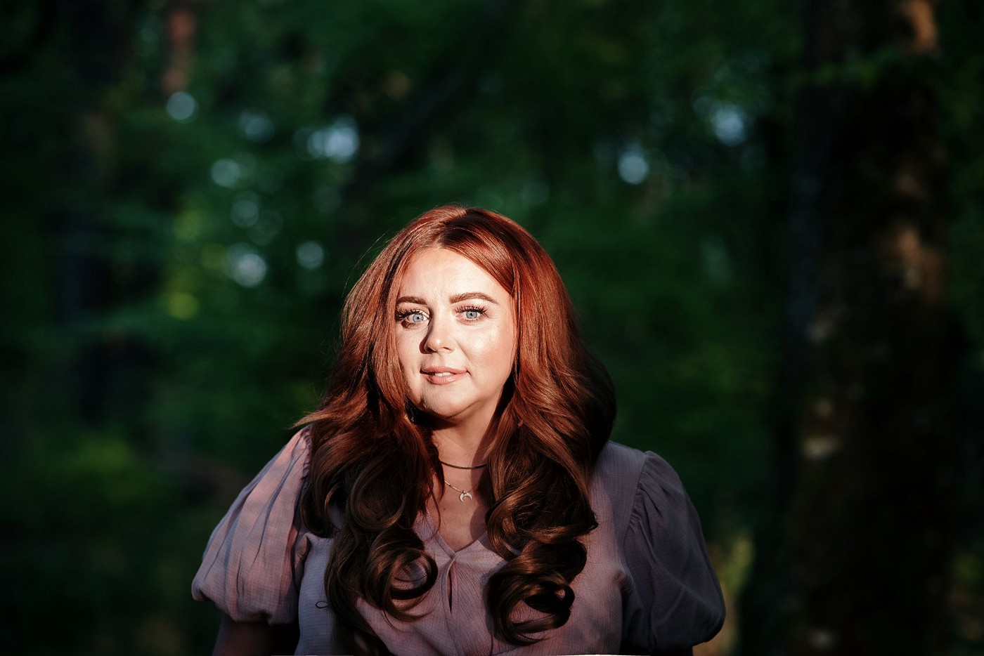 Close-up of attractive, vibrant woman in dusky pink blouse and long thick locks of red hair, standing in a shaded forest. Spotlight is on her face. By photographer Lisa McConnellogue. Ciara McCarron from Derry, Northern Ireland, is a Trauma-Informed Coach, Mentor & Therapist, Hypnotherapist and Founder of Redesign Your Vibe.