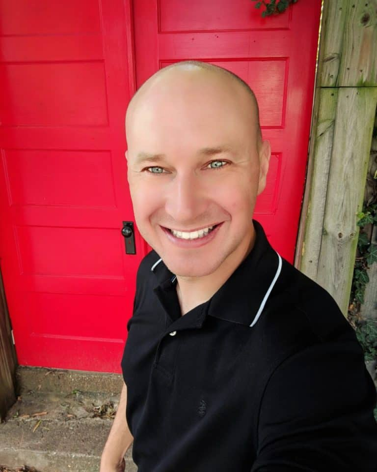 A very bald christopher kokoski standing in front of a very red door.