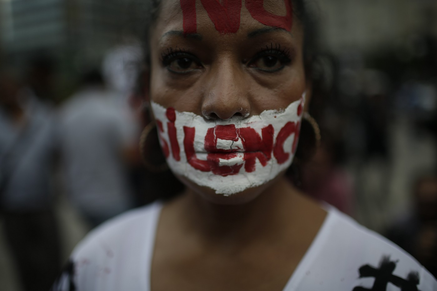 A woman with writing on her face that reads 'no to silence' looks at the camera during a demonstration in Mexico.