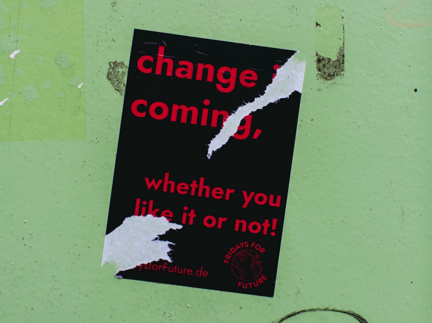 Torn poster on a green wall saying: Change is coming. whether your like it or not!