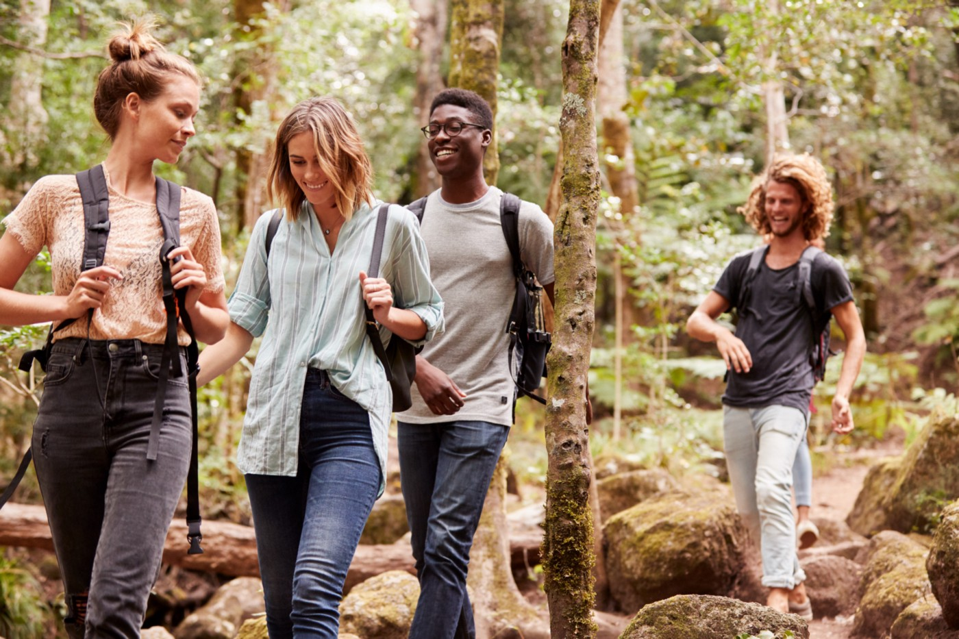 Four people with backpacks share a laugh while walking through a wooded area.