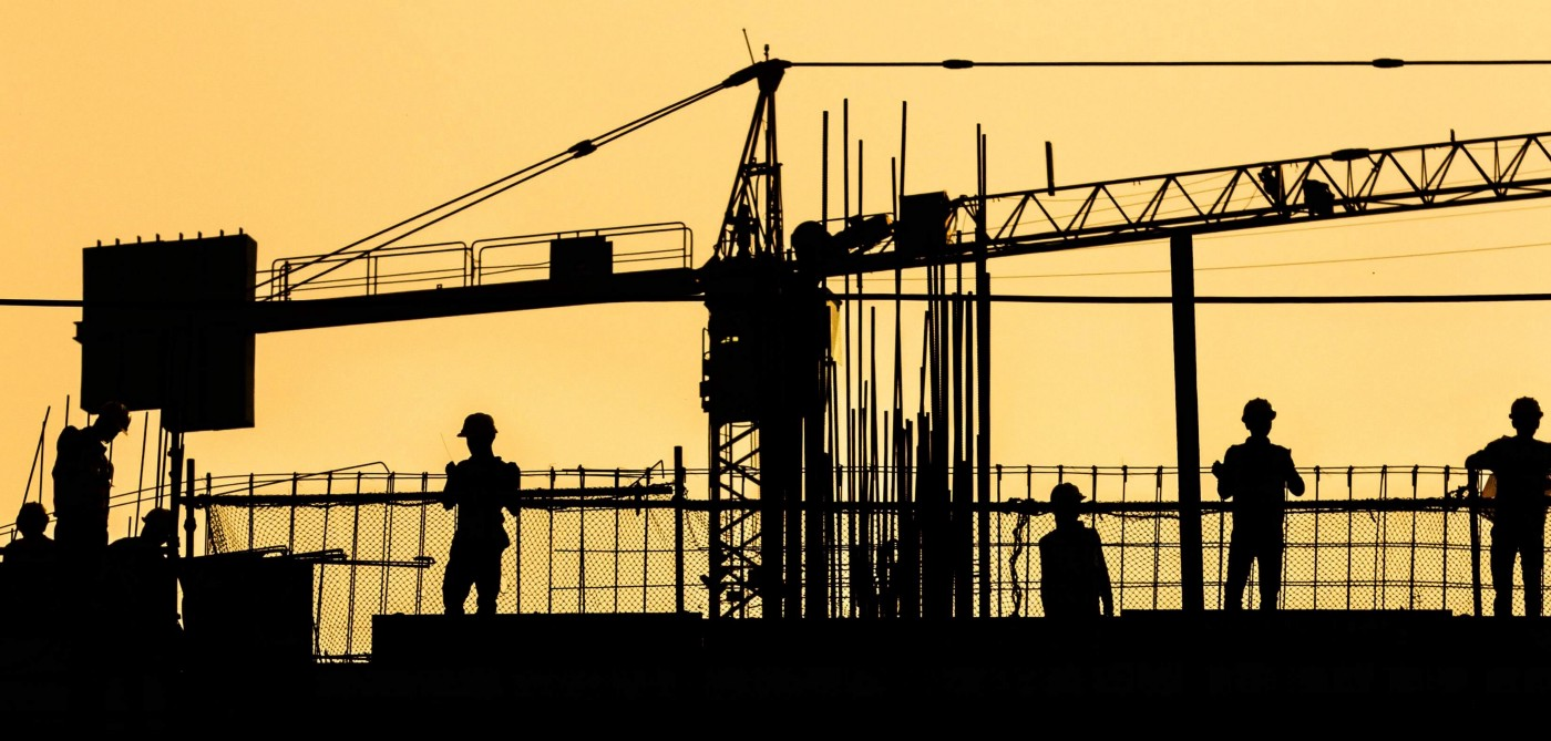 A silhouette of a building crane and three construction workers against a pale yellow sky