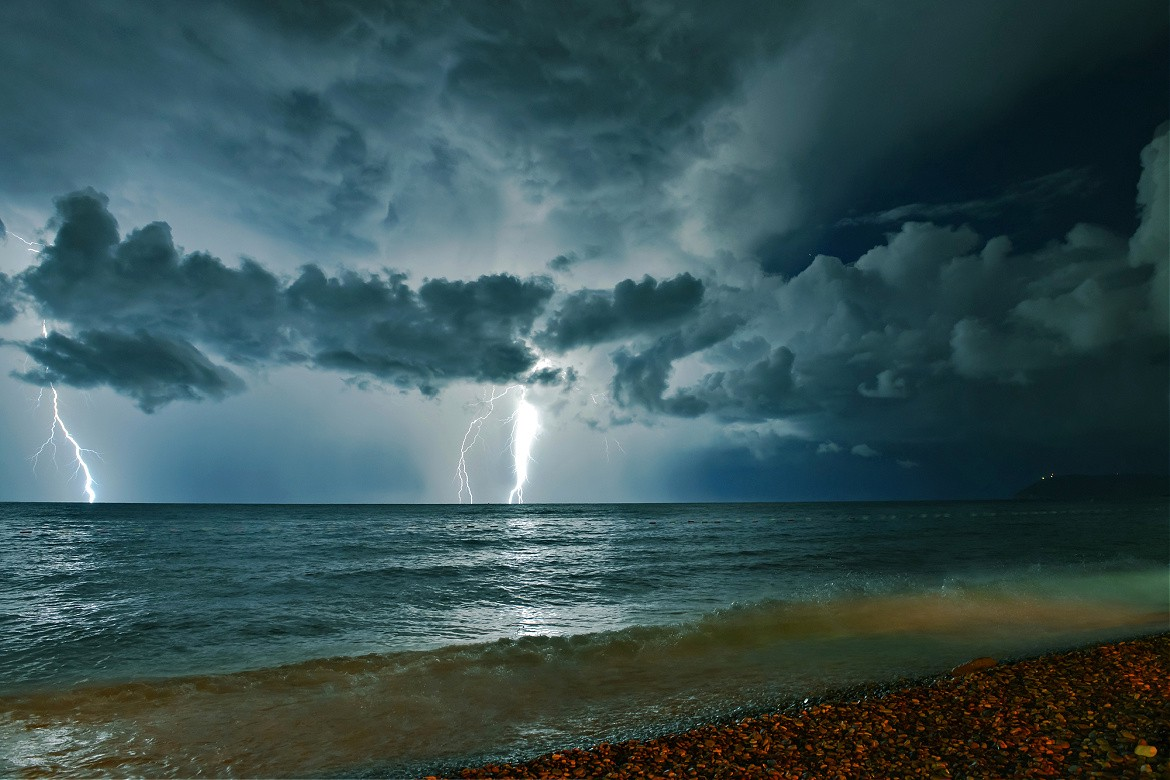 Lightening over the sea, through a dark and cloudy sky