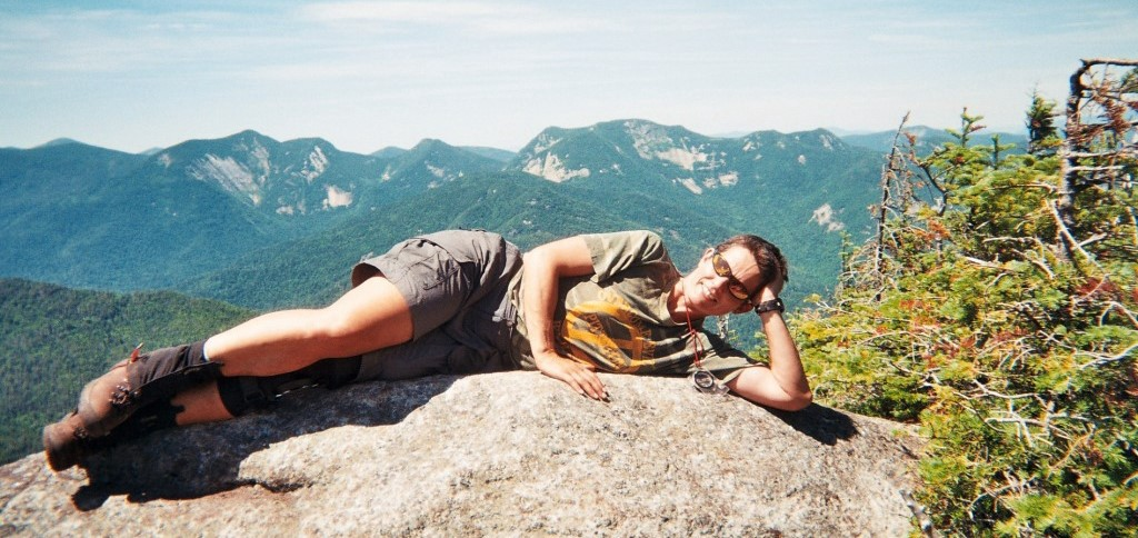 woman laying on a summit rock