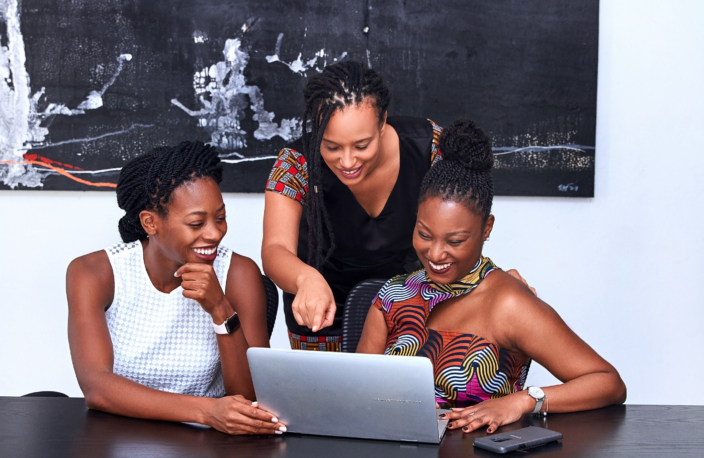 Image of three women collaborating on a project on a laptop.