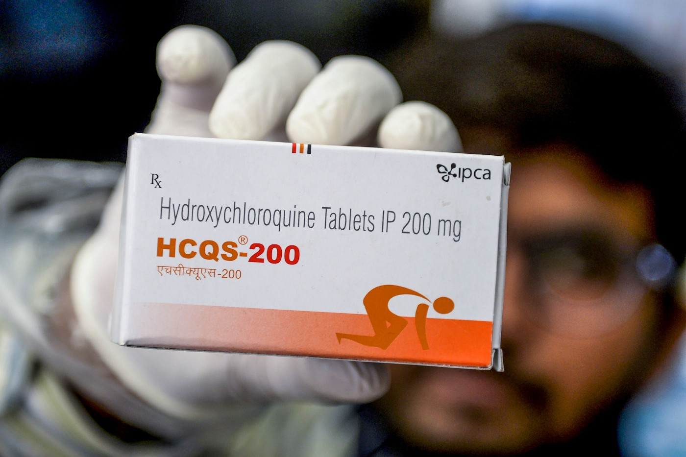 A pharmacist displays a box of hydroxychloroquine tablets.
