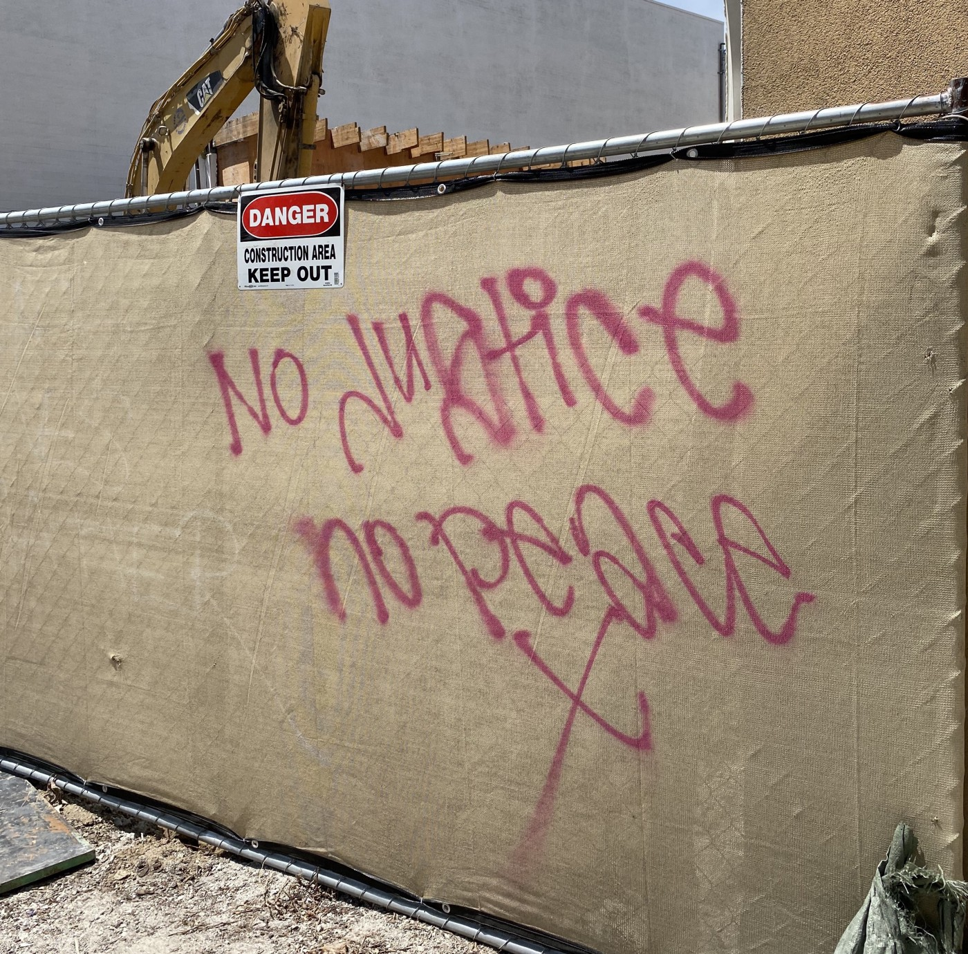 "Graffiti outside of a construction site saying ""No justice no peace X"""
