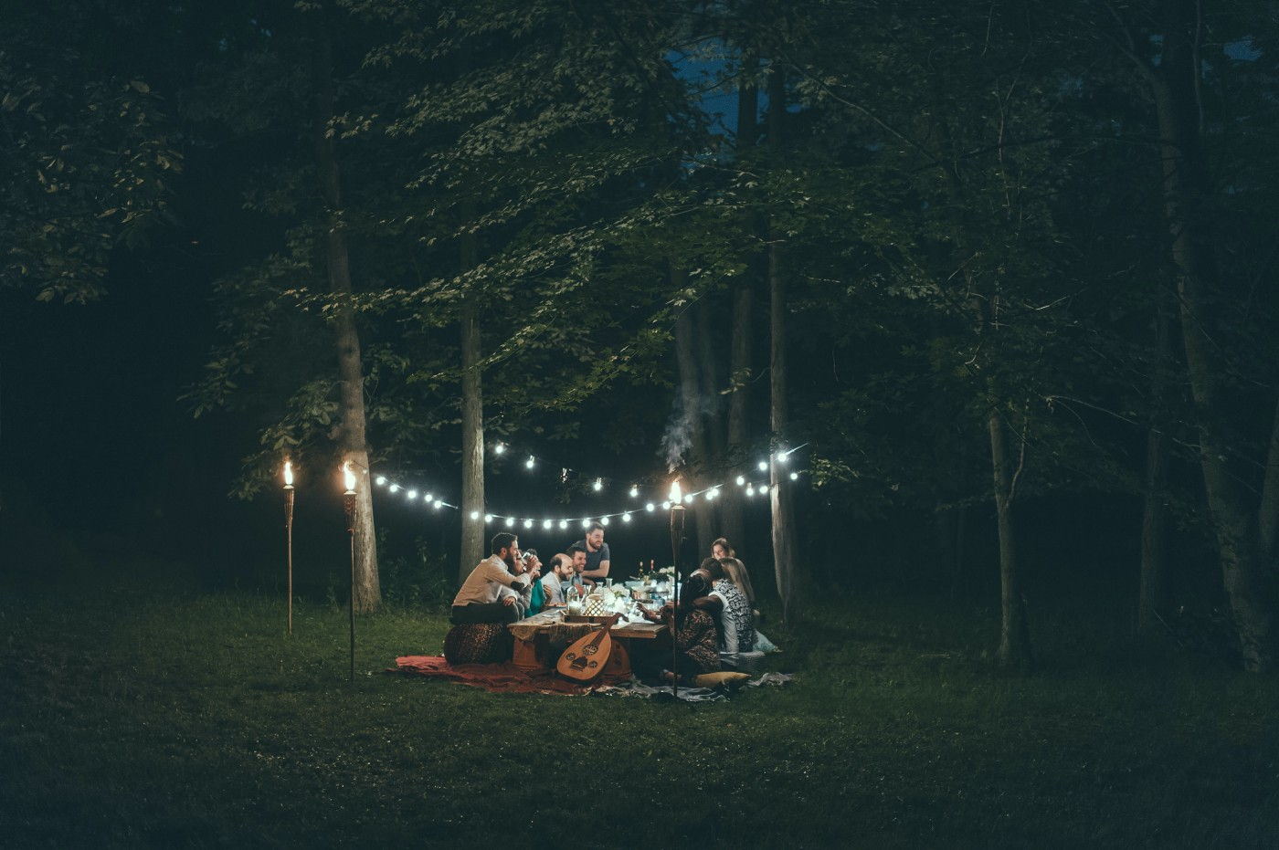 Friends at a forest dinner party with guitar, torches, lights strung between the trees.