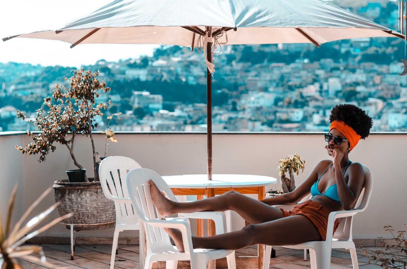 Black woman sitting at a table with her feet up, on a balcony