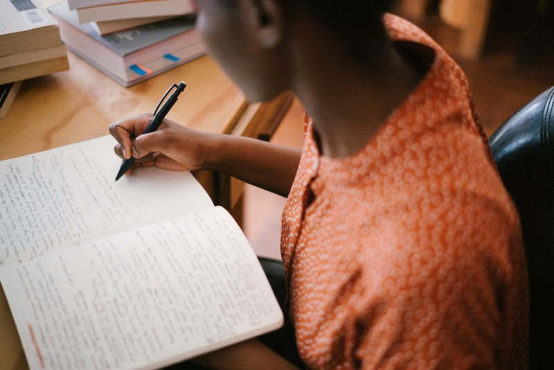 A Black woman writes with a pen in a notebook at a desk