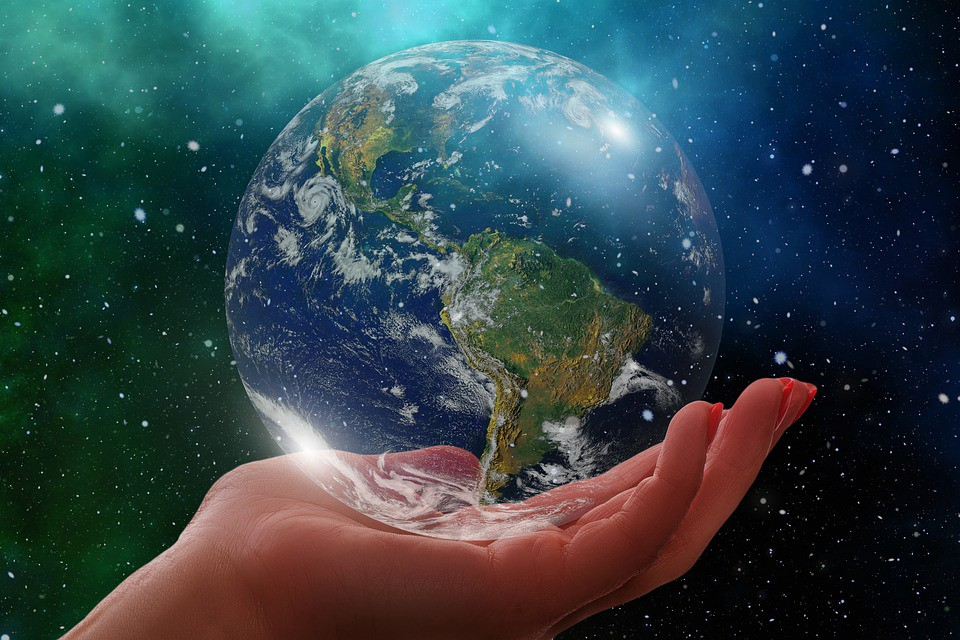 Picture of globe of the world held in the palm of a hand.