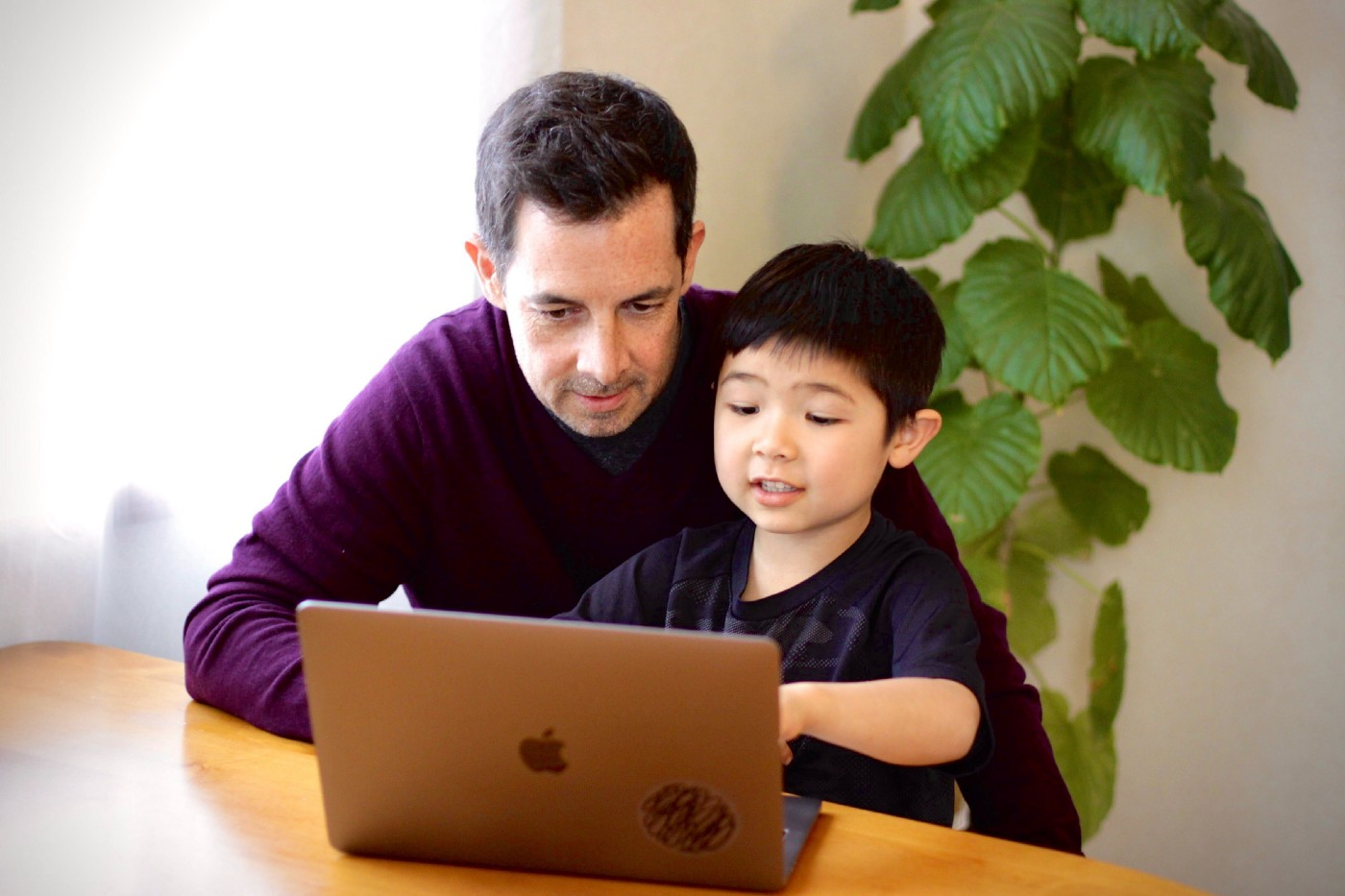 Father and son work together on a laptop computer at the dining table.