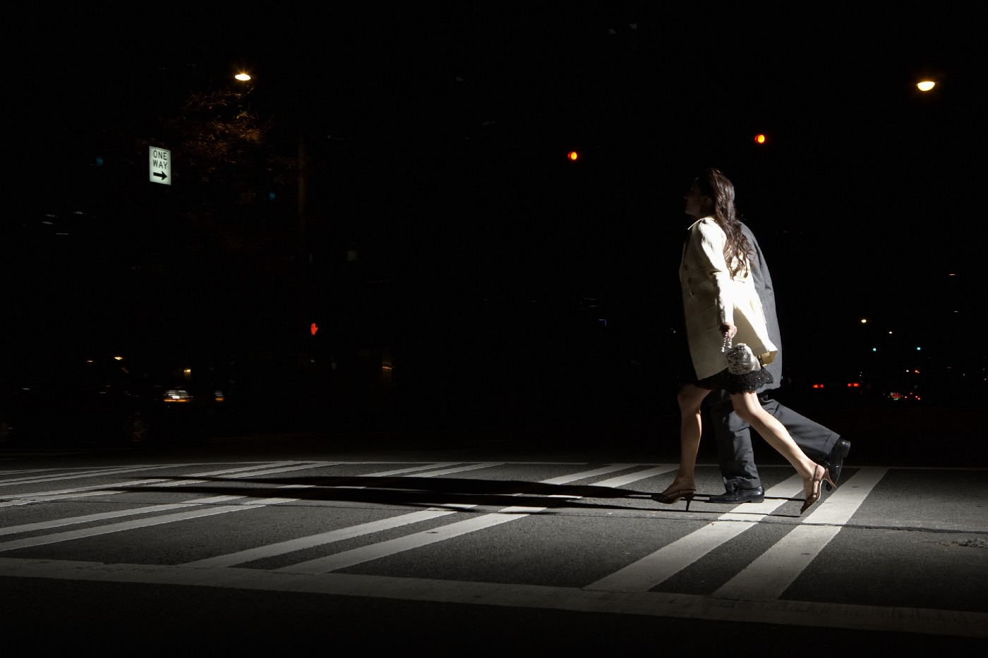 Side view of a young man and woman crossing the street at night.