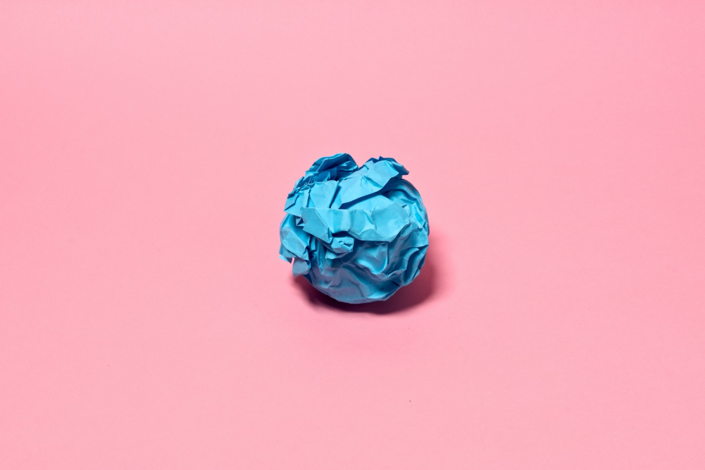 A crumpled ball of blue paper against a solid pink background.