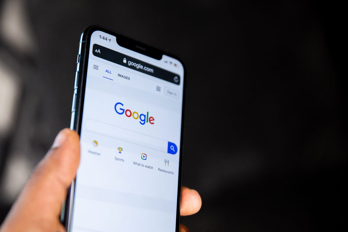 Hand holding phone with google.com displayed on the screen