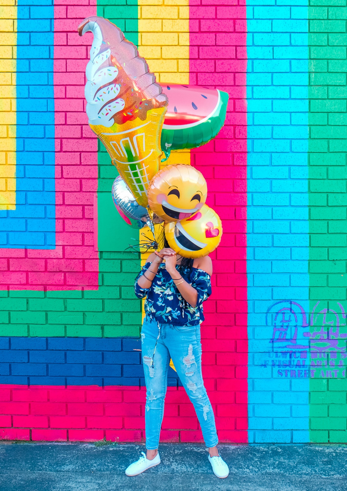 Woman holding balloons that show happy faces.