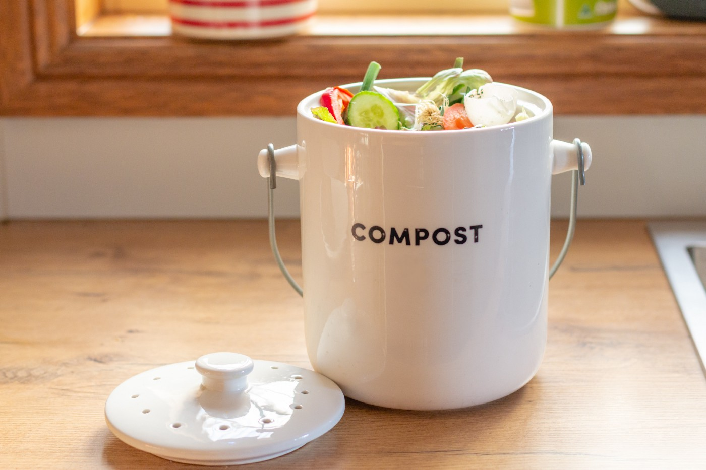 A cleanly-designed ceramic compost bin sitting on a kitchen counter