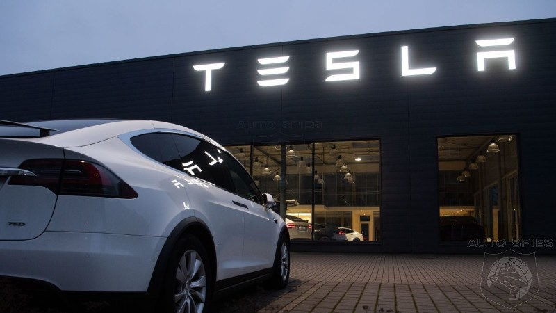 A photo of a Tesla car parked in front of a building with a Tesla signage