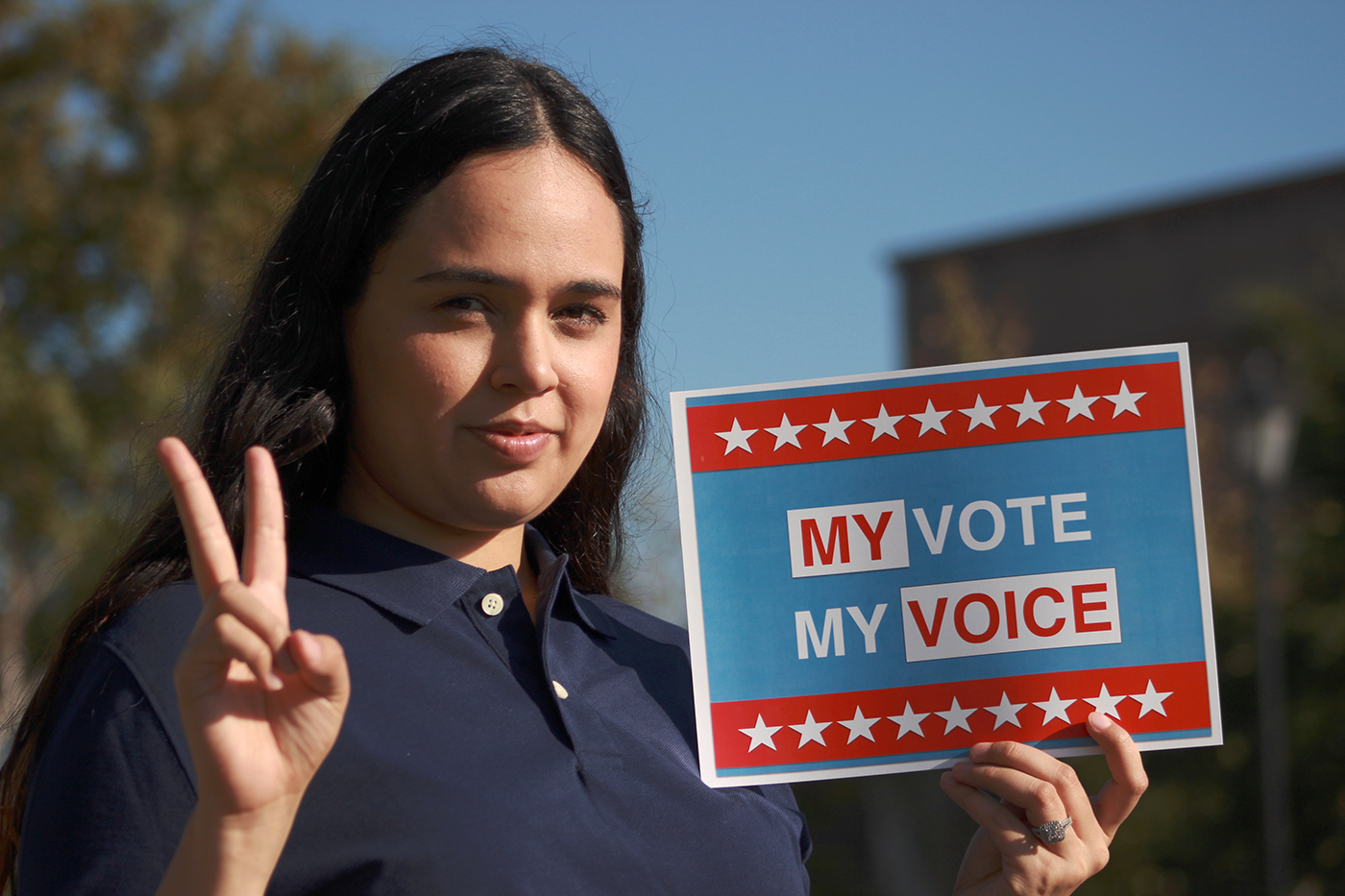 "A young Latina woman makes a peace sign with her right hand and holds a sign in her land hand that reads ""My Vote, My Voice."""