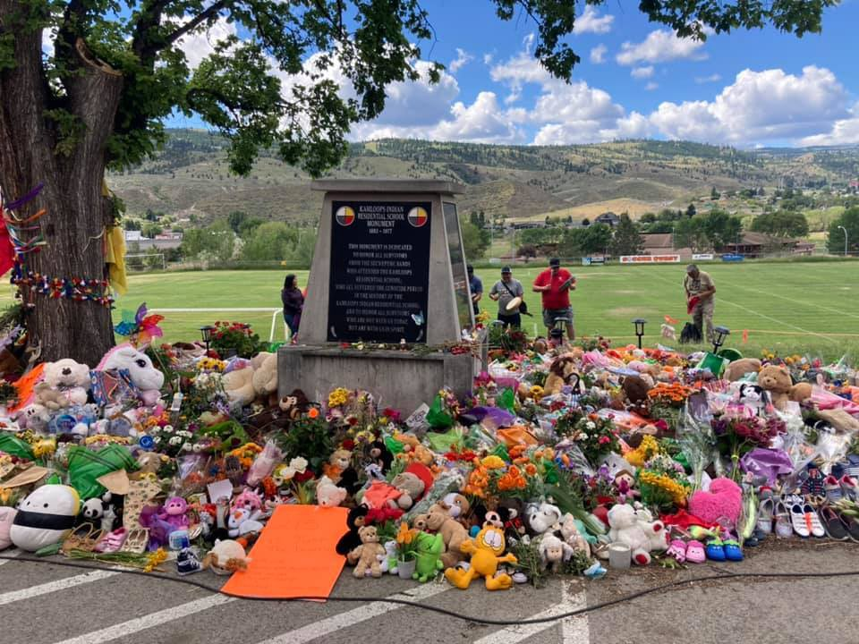 Memorial with flowers and indigenous community members honouring the lives of the 215 children lost at the Kamloops Residential School