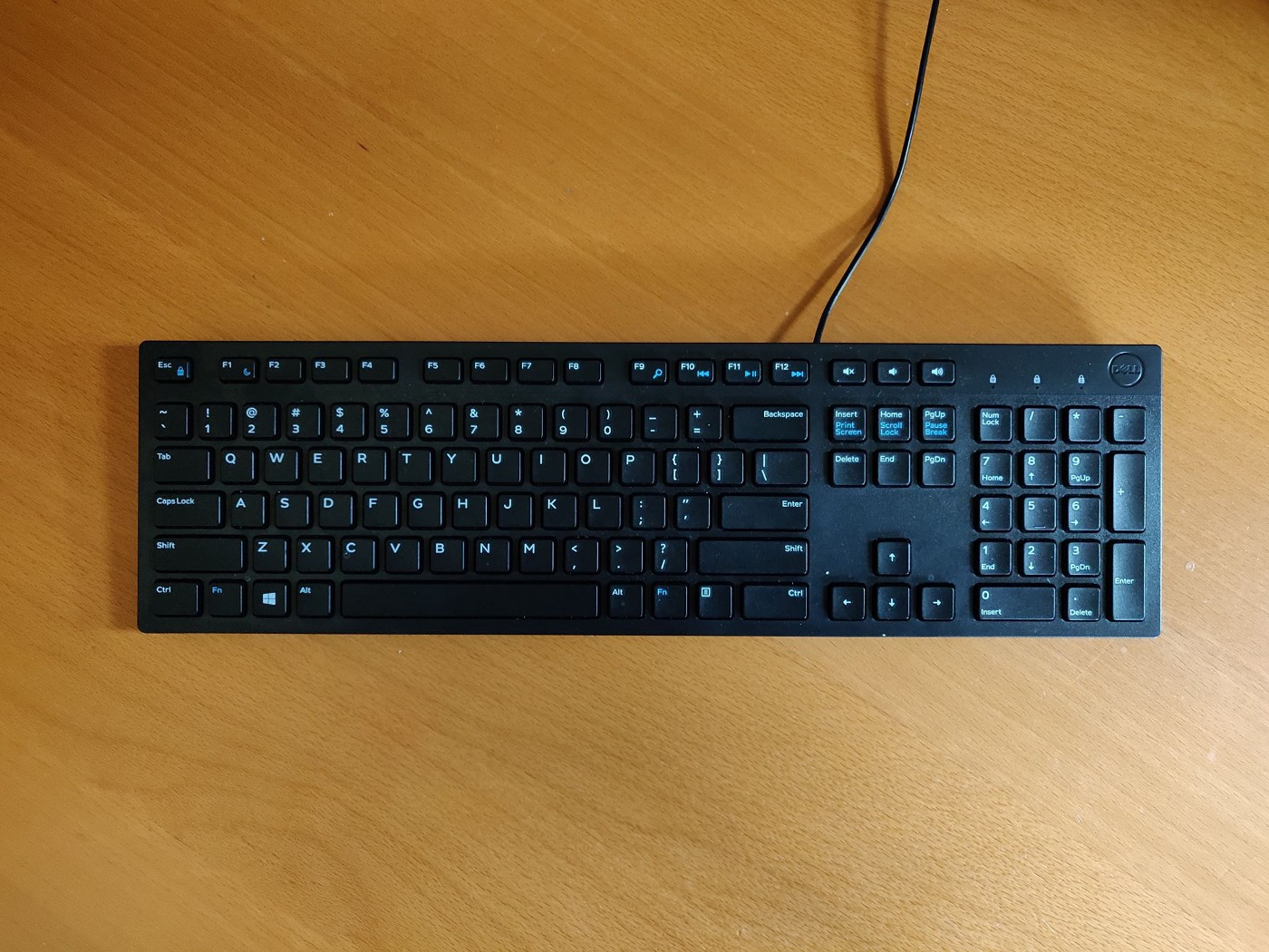 Top down view of a black keyboard with a minimal wooden desk.